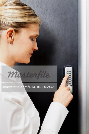 Woman pressing door keypad Stock Photo - Premium Royalty-Free, Image code: 614-06043932