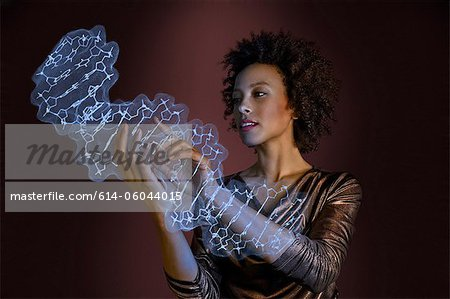 Woman interacting with holographic genome Stock Photo - Premium Royalty-Free, Image code: 614-06044015