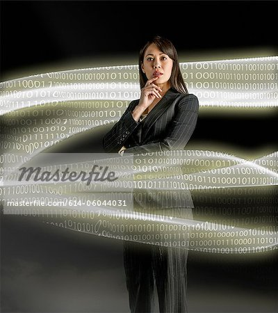 Businesswoman looking at data streams Stock Photo - Premium Royalty-Free, Image code: 614-06044031