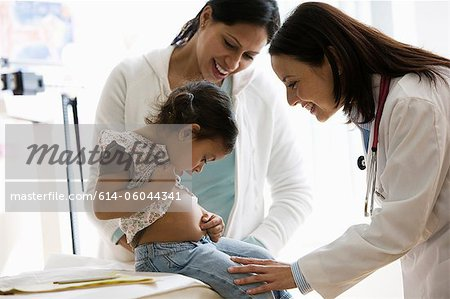 Doctor examing young girl in office Stock Photo - Premium Royalty-Free, Image code: 614-06044341