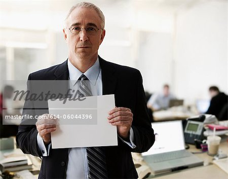 Portrait of senior man holding blank sheet of paper Stock Photo - Premium Royalty-Free, Image code: 614-06044396