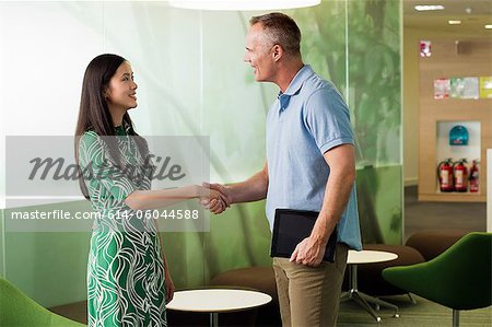Mature man shaking hands with young woman in meeting Stock Photo - Premium Royalty-Free, Image code: 614-06044588