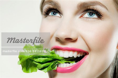 Young woman biting lettuce Stock Photo - Premium Royalty-Free, Image code: 614-06116191