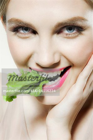 Young woman biting lettuce Stock Photo - Premium Royalty-Free, Image code: 614-06116224