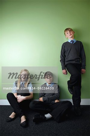 Three surly school children looking at camera Stock Photo - Premium Royalty-Free, Image code: 614-06116430