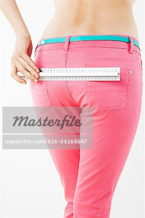 Young woman measuring buttocks Stock Photo - Premium Royalty-Free, Image code: 614-06168647