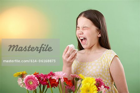 Girl with flowers sneezing Stock Photo - Premium Royalty-Free, Image code: 614-06168873