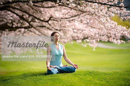 Woman in lotus position under cherry tree Stock Photo - Premium Royalty-Free, Image code: 614-06168930