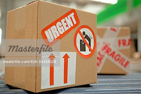 Cardboard box with warning stickers on conveyor belt Stock Photo - Premium Royalty-Free, Image code: 614-06169128