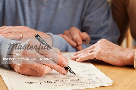 Senior man signing will Stock Photo - Premium Royalty-Free, Image code: 614-06169296