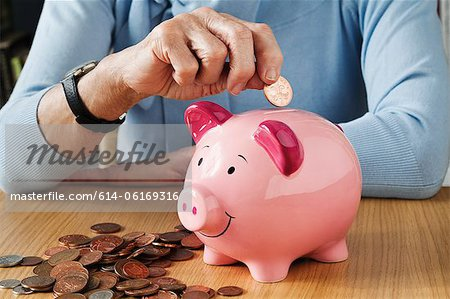 Senior woman inserting coins into piggybank Stock Photo - Premium Royalty-Free, Image code: 614-06169316