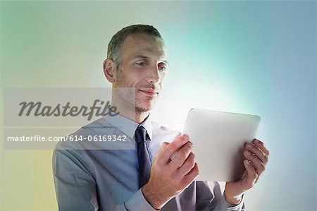 Businessman using digital tablet with lights Stock Photo - Premium Royalty-Free, Image code: 614-06169342
