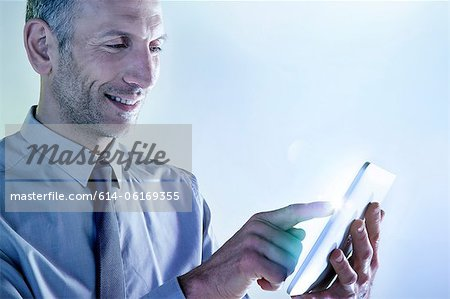 Businessman using digital tablet with lights Stock Photo - Premium Royalty-Free, Image code: 614-06169355