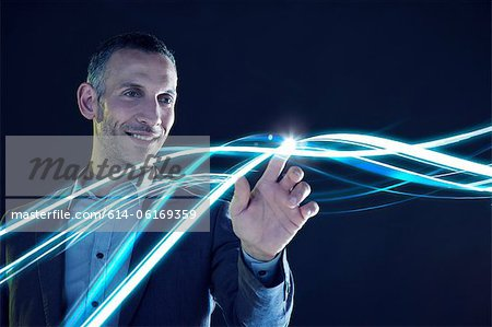 Businessman touching lines of light Stock Photo - Premium Royalty-Free, Image code: 614-06169359