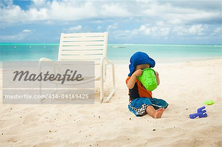 Little boy at the beach, looking into a bucket Stock Photo - Premium Royalty-Free, Image code: 614-06169425