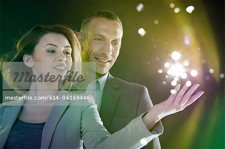 Businesspeople reaching out to lights Stock Photo - Premium Royalty-Free, Image code: 614-06169446