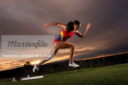 Female athlete moving off from starting blocks Stock Photo - Premium Royalty-Free, Image code: 614-06169456