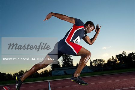 Male athlete leaving starting blocks Stock Photo - Premium Royalty-Free, Image code: 614-06169463