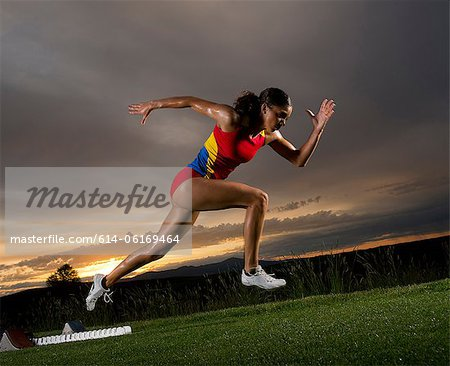 Female athlete leaving starting blocks Stock Photo - Premium Royalty-Free, Image code: 614-06169464