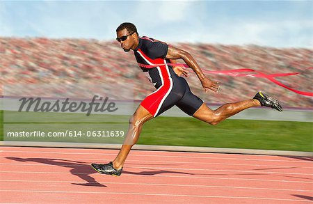 Runner crossing the finish line Stock Photo - Premium Royalty-Free, Image code: 614-06311639