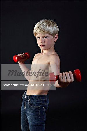Boy lifting hand weights Stock Photo - Premium Royalty-Free, Image code: 614-06311719