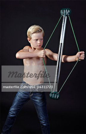 Boy using chest expander Stock Photo - Premium Royalty-Free, Image code: 614-06311723