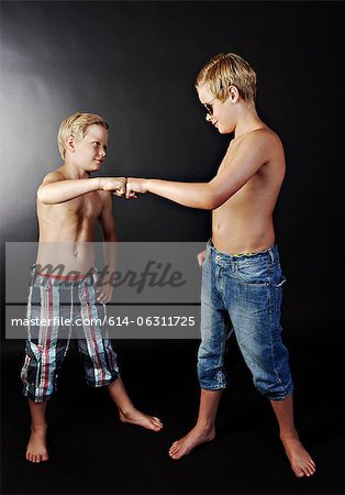 Brothers doing high five with fists Stock Photo - Premium Royalty-Free, Image code: 614-06311725