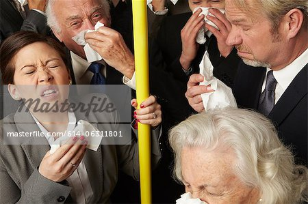 Businesspeople sneezing on subway train Stock Photo - Premium Royalty-Free, Image code: 614-06311801