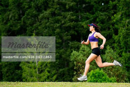 Young woman running in park Stock Photo - Premium Royalty-Free, Image code: 614-06311863