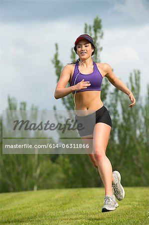 Young woman running in park Stock Photo - Premium Royalty-Free, Image code: 614-06311866