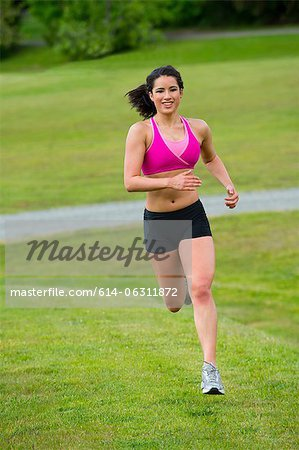 Young woman running in park Stock Photo - Premium Royalty-Free, Image code: 614-06311872
