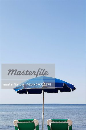 Blue parasol and sun loungers by the sea Stock Photo - Premium Royalty-Free, Image code: 614-06311878