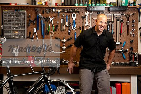 Man laughing in bicycle repair shop Stock Photo - Premium Royalty-Free, Image code: 614-06311986