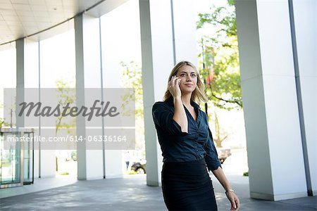 Businesswoman in front of office on cellphone Stock Photo - Premium Royalty-Free, Image code: 614-06336164