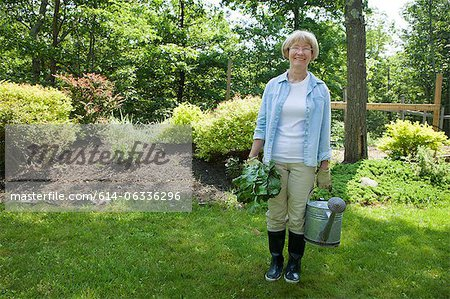 Woman with watering can and beetroot in garden Stock Photo - Premium Royalty-Free, Image code: 614-06336296