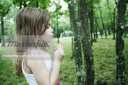Girl blowing bubbles in forest Stock Photo - Premium Royalty-Free, Image code: 614-06336304