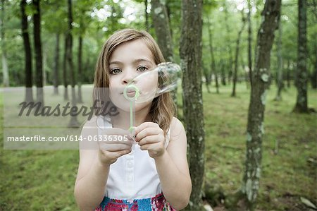 Girl blowing bubbles in forest Stock Photo - Premium Royalty-Free, Image code: 614-06336305