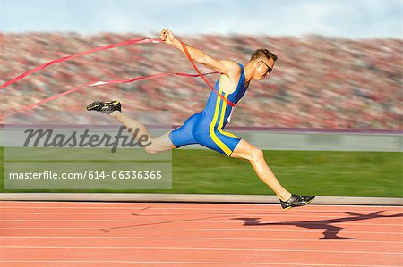 Runner crossing the finish line Stock Photo - Premium Royalty-Free, Image code: 614-06336365