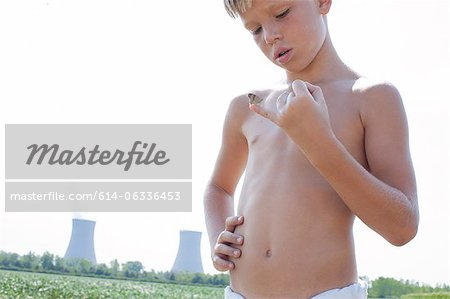 Boy holding butterfly on little finger with nuclear power station in background Stock Photo - Premium Royalty-Free, Image code: 614-06336453