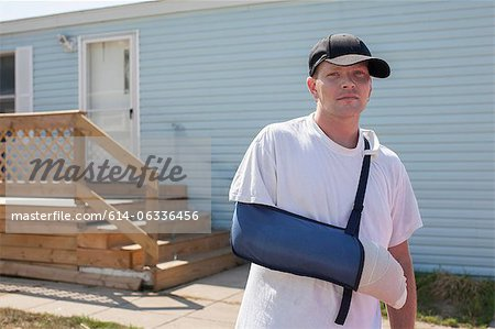 Man outside house with arm in sling Stock Photo - Premium Royalty-Free, Image code: 614-06336456