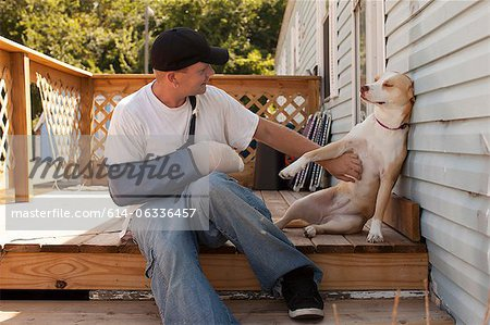 Man outside house with arm in sling and dog Stock Photo - Premium Royalty-Free, Image code: 614-06336457