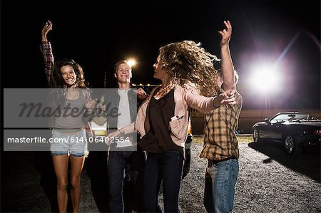 Four friends in parking lot at night Stock Photo - Premium Royalty-Free, Image code: 614-06402554