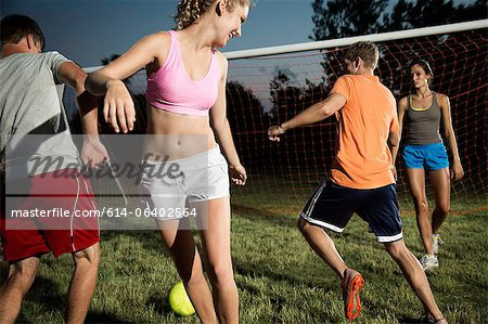 Friends playing soccer at night Stock Photo - Premium Royalty-Free, Image code: 614-06402564