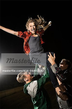 Two male friends lifting teenage girl, arms outstretched Stock Photo - Premium Royalty-Free, Image code: 614-06402592