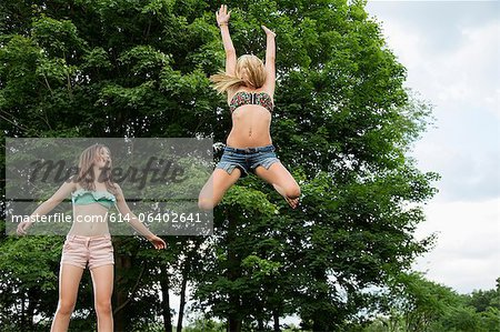 Two girls on trampoline Stock Photo - Premium Royalty-Free, Image code: 614-06402641