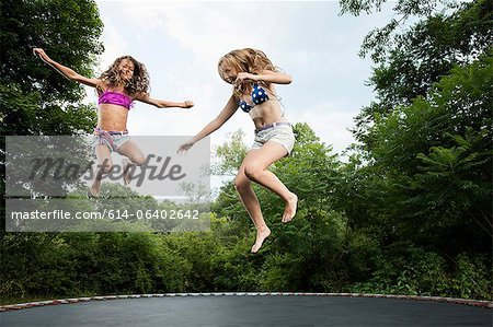 Two girls on trampoline Stock Photo - Premium Royalty-Free, Image code: 614-06402642