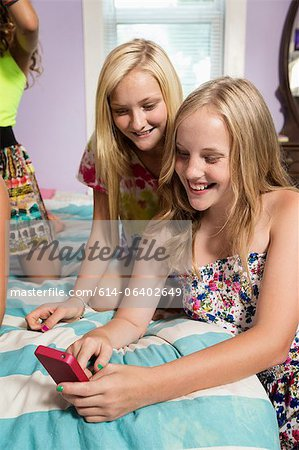 Girls using smartphone in bedroom Stock Photo - Premium Royalty-Free, Image code: 614-06402649