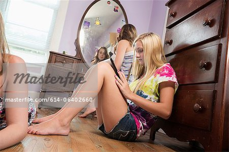 Girl sitting on bedroom floor with digital tablet Stock Photo - Premium Royalty-Free, Image code: 614-06402660
