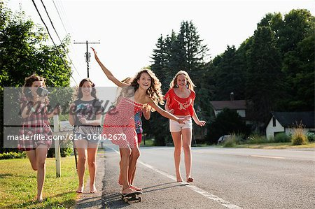 Girl on skateboard with friends Stock Photo - Premium Royalty-Free, Image code: 614-06402670