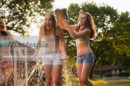 Girl pouring bucket of water over friend's head Stock Photo - Premium Royalty-Free, Image code: 614-06402688
